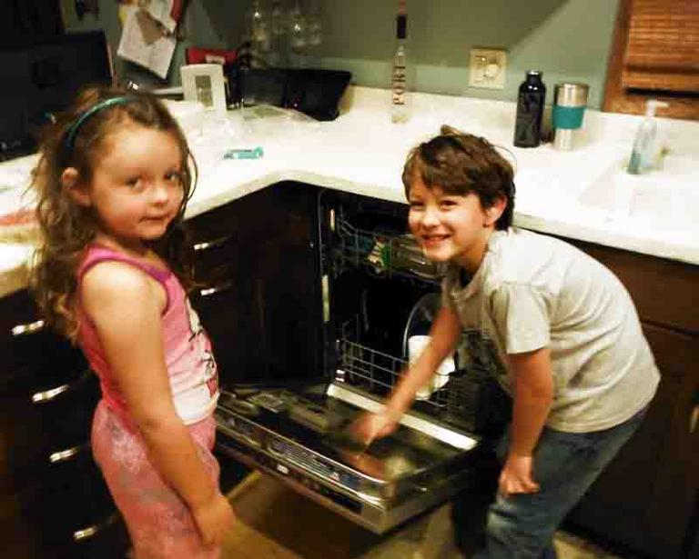Children taking bacterial samples from dirty dishes in dishwasher