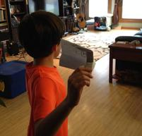 Boy preparing to test a paper airplane.